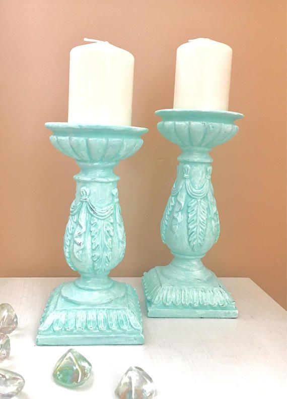Gorgeous set of 2 large pillar candle holders with white Candles includes! Finished in a gorgeous shades of aqua and white with a unique chalkpainted technique. This lovely set is very heavy, I believe it is plastered, with beautufil intricate details enhanced by the paint. The taller one