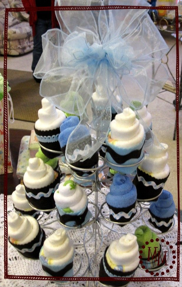 """A tower of """"cupcakes"""" from baby washcloths and diapers    They're wrapped with felt and decorative ribbon."""