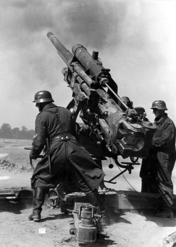 A heavy caliber 8,8 cm anti aircraft armament is firing at hostile war planes.