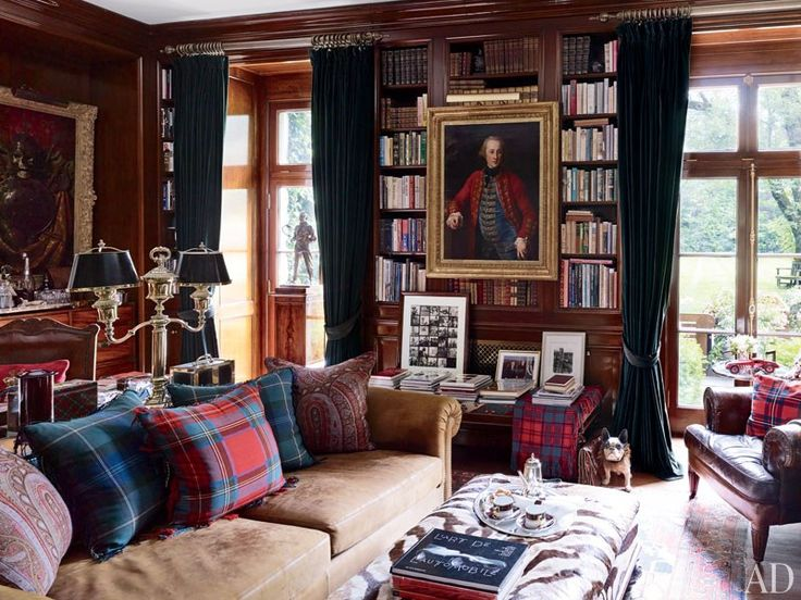 A circa-1774 portrait by Pompeo Girolamo Batoni is displayed between the library's French doors, which are curtained with a Ralph Lauren Home velvet; the two-arm Argand lamp is 19th century, and the pillows are made of antique fabrics.