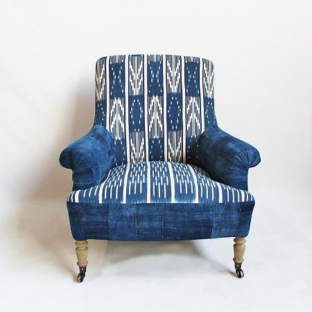 Vintage African Ikat hand dyed indigo fabric with Mali mud cloth upholstered arms. Raw elm wood legs on casters.