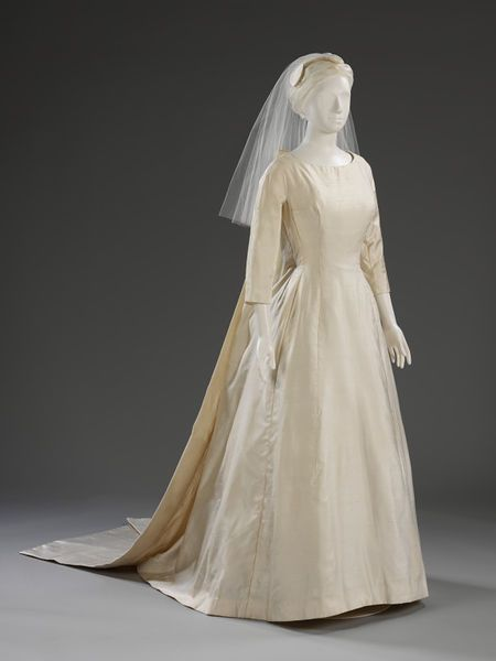 Ivory wedding dress and headdress made of shantung silk. The dress is floor-length and has a two-piece train which detaches at the neck. l Victoria and Albert Museum