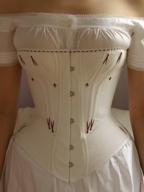 TIETOJA MINUSTA: The is a one layer cotton coutil corset, sewn with machine using period techniques described in The Fashions Of The Gilded Age by Frances Grimble. The pattern is based on the c. 1873 corset from Corsets and Crinolines by Norah Waugh. The corset is heavily corded with cotton cord, which stiffens the corset wonderfully.