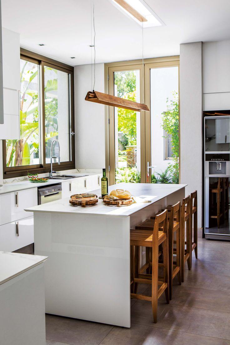 Cocina súper luminosa, con gran ventanal y puerta vidriada que sale al patio de acceso. Mesadas de Dekton imitación Calacatta, y piso de porcelanato Ilva 'Marmi'.