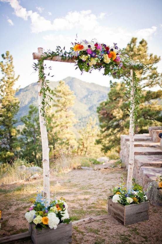 A rustic wedding arch with colorful wildflower decorations built into planter boxes to brighten up any outdoor wedding.