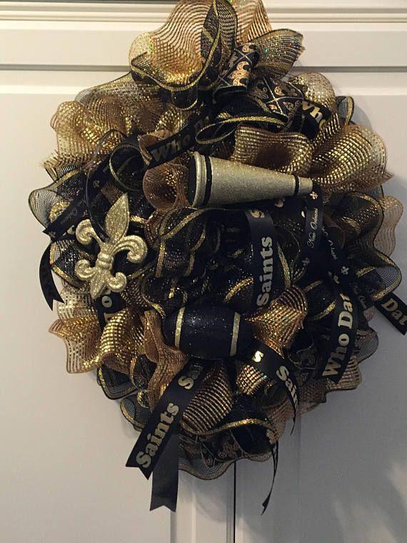 This is a 19 wide X 24 high mesh Saints wreath. Black and gold mesh, lots of Saints ribbons, megaphone, football, flour de lis. Who dat