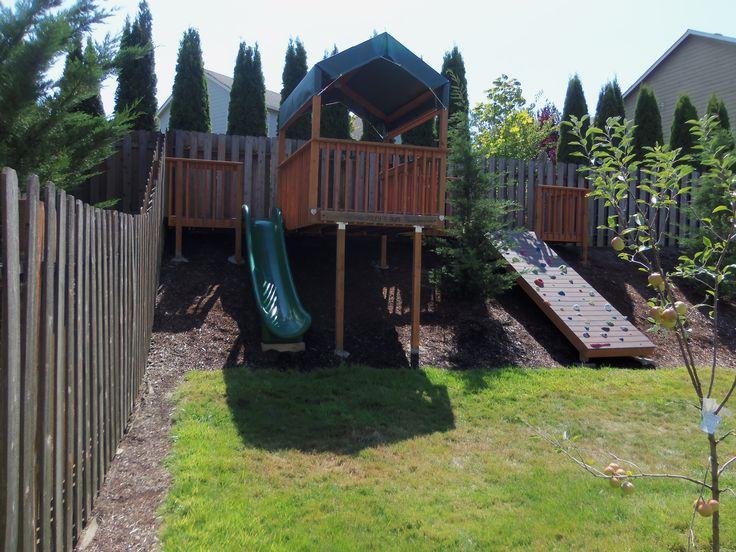 Backyard hillside rock wall, slide and play area, sloped yard