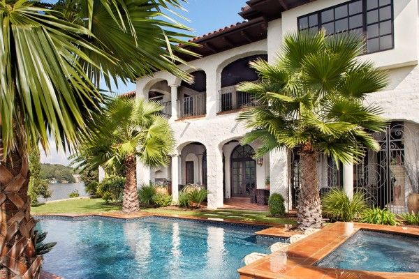 Mature palm trees frame the entrance to the pool and the rear entrance to the home.