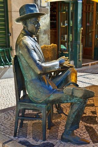 Fernando Pessoa, el poeta misterioso  Via Condé Nast Traveler España  En el Montmartre de Lisboa, el Chiado, Fernando Pessoa se movía a principios del siglo XX como pez en el agua entre cafés y tertulias literarias. Sus poesías, firmadas por su pléyade de heterónimos, constribuyeron a crear el misterioso halo que lo envuelve hoy. Acércate a la rua Garrett y sientate a su vera en la terraza de A Brasileira a ver si suelta prenda y consigues desvelar el secreto.   #Portugal