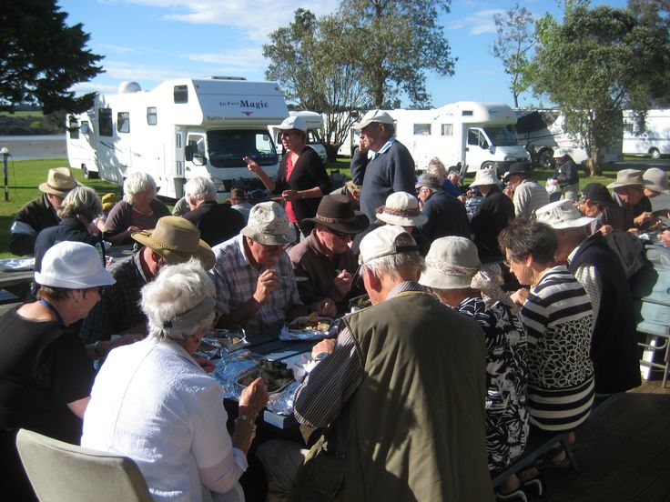 A group of campers enjoying a steamed Hangi dinner during a stay at Waitangi Holiday Park