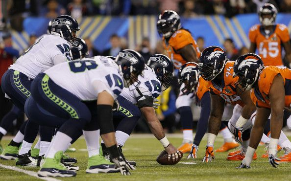 Russell Wilson Photos Photos - The Seattle Seahawks and the Denver Broncos line up during Super Bowl XLVIII at MetLife Stadium on February 2, 2014 in East Rutherford, New Jersey. - Super Bowl XLVIII - Seattle Seahawks v Denver Broncos