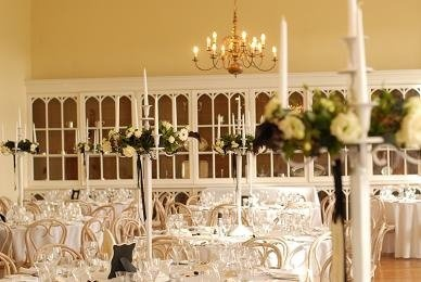 Ivory Candelabra in the Ballroom at Brympton House, dressed with floral rings and hanging name tags