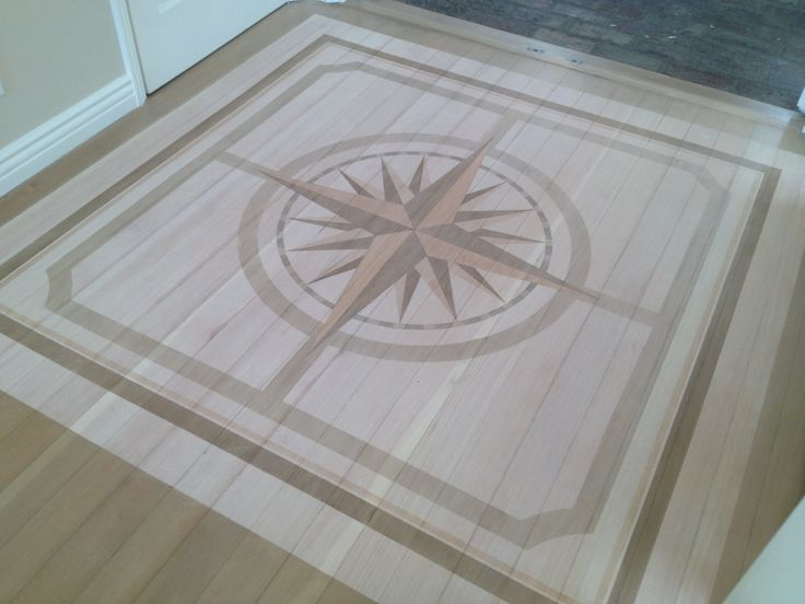 Compass Rose painted on hardwood floor by artist Allison Cosmos