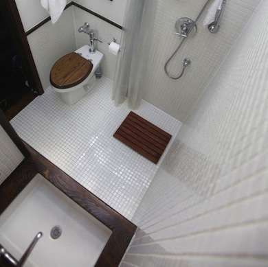 All-In-One - the shower is incorporated right into the greater overall space in this diminutive bathroom. White 1x1 inch tile is used on both the floor and walls throughout to bring it all together, while a dark wood counter, bath mat & toilet seat bring warmth to the room (teak or other water resistant)