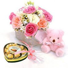 Ten cheerful roses arranged in a basket with a box of chocolate(8T) and a lovely small bear
