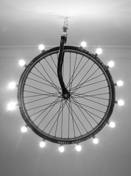 Use an old bike tire/wheel and connect LED household bulbs through wire in the tire tube. Then hang from the ceiling! Creative lighting design.