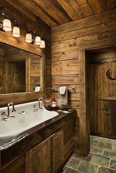 Love the farm house sink. The Winkels went rustic and whimsical in the basement bathroom. The door with the crescent moon leads to a bathroom designed to resemble an outhouse. Guests are relieved to discover modern plumbing.