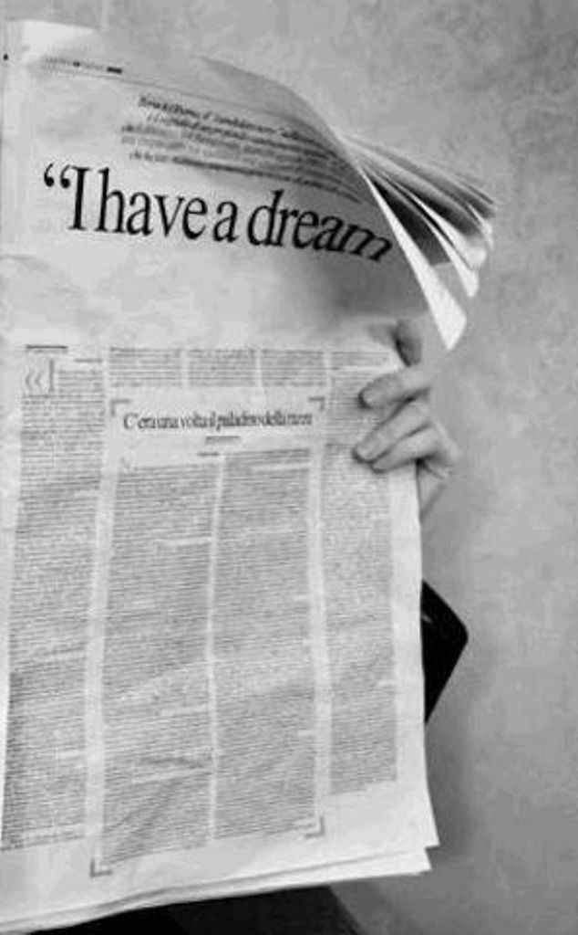 """Black and White image of someone behind a newspaper with headline, """" I have a dream..'"""