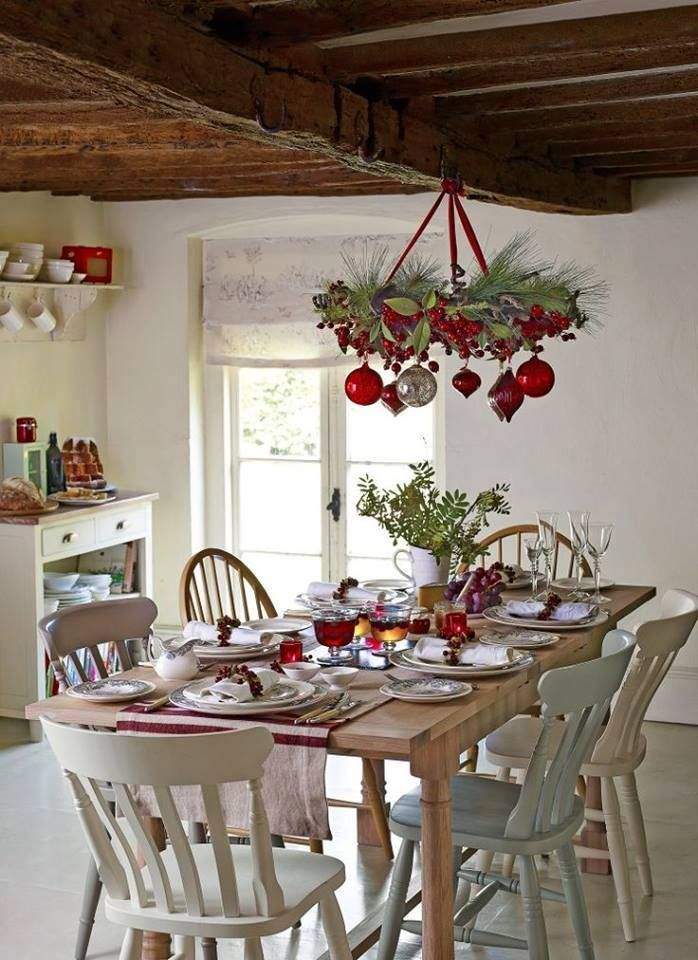 white cottage dining room with green and ornaments festooned on chandelier