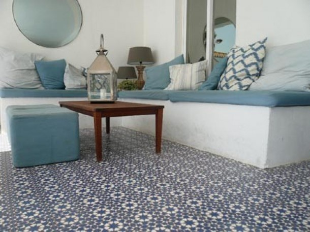Portugese tiles on terrace. bench made of white painted concrete