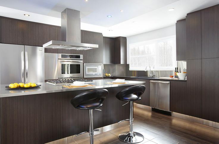 Îlot et armoires de cuisine réalisés en mélamine. Comptoir en granit et acier inoxydable.