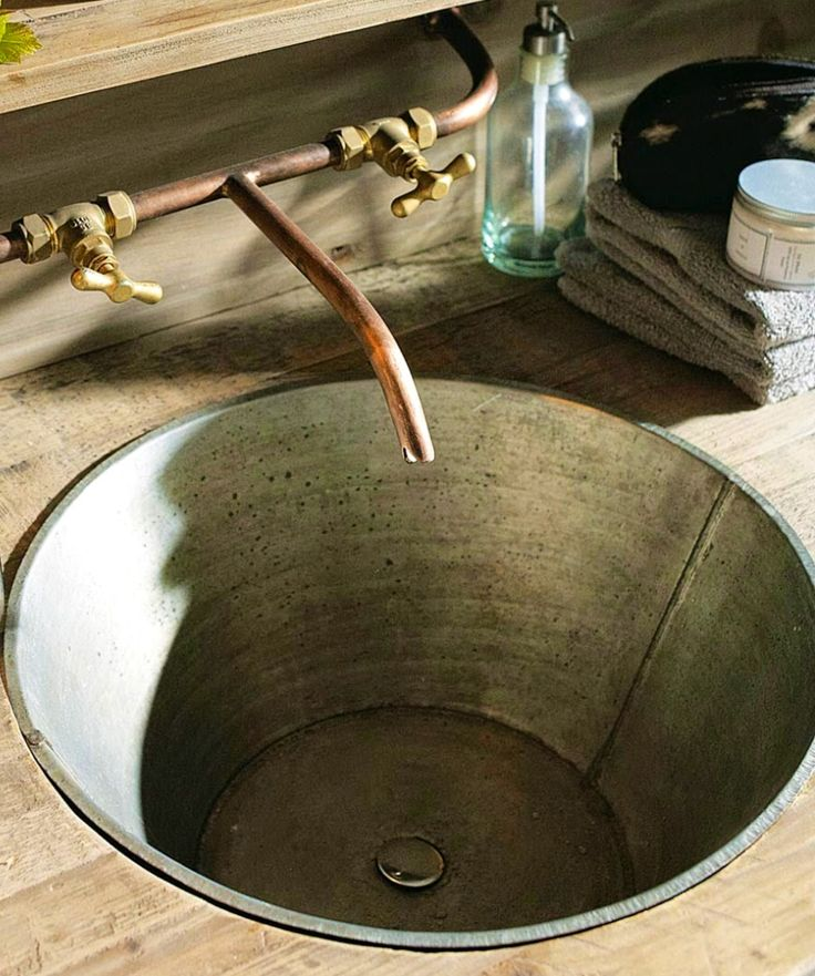 The charm of wood recycled in the bathroom. Aged basin sink. Zinc and copper taps.