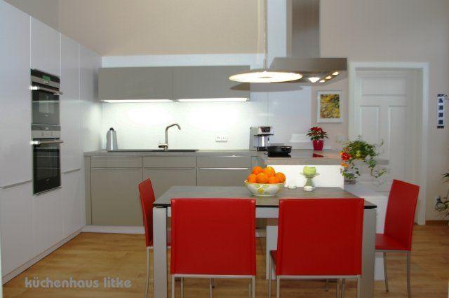 Küche von LEICHT mit Halb-Insel, Tisch und Stühle von Calligaris, Dunsthaube O+F mit Plasmanorm-Filter, Hängeschränke mit Unterbodenbeleuchtung