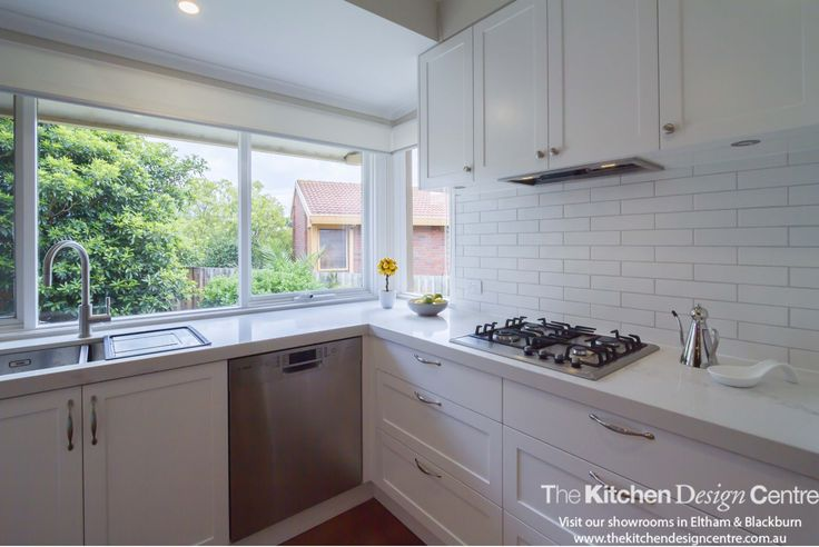 A modern take on a traditionally inspired kitchen. Large, open bay or corner  windows to let in lots of light and an open servery to practical service into the dining room. An elegant white kitchen and laundry. www.thekitchendesigncentre.com.au @thekitchen_designcentre