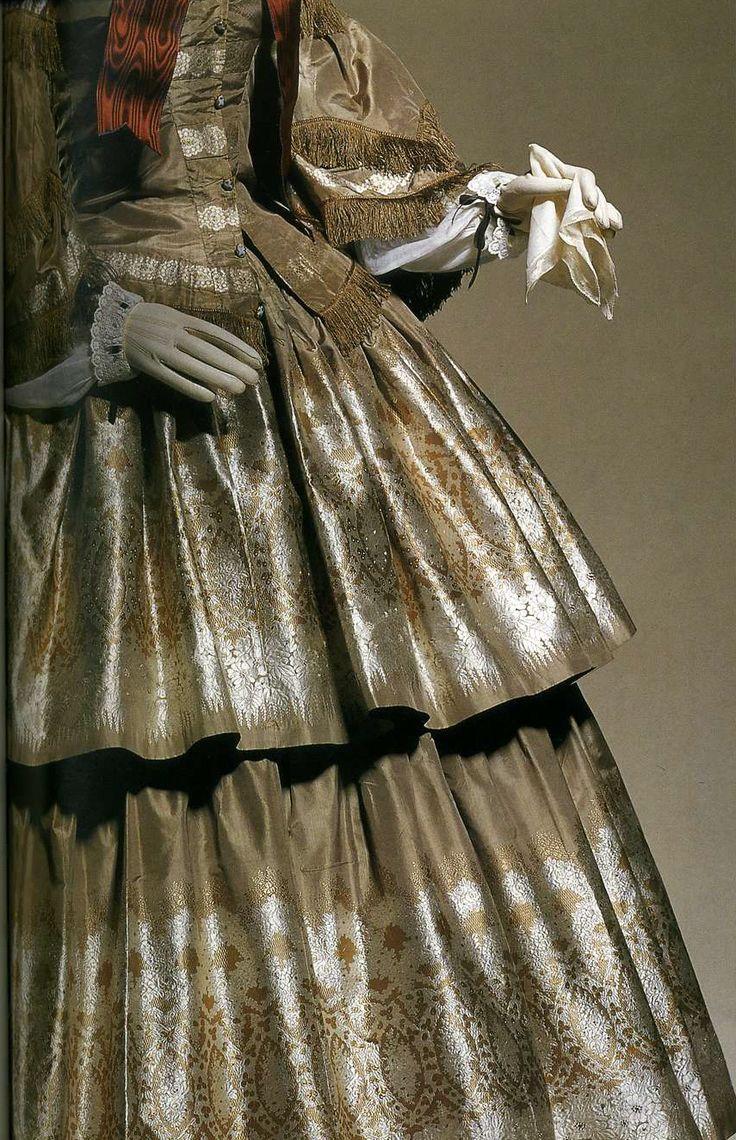 """Дневное платье. Около 1855. Серебристо-серая шелковая тафта-брокад с узором, имитирующим серебристое кружево и цветы, бахрома по нижней части корсажа и двойных рукавов """"пагода"""", белое кружево на шее, юбка с двумя рядами воланов."""