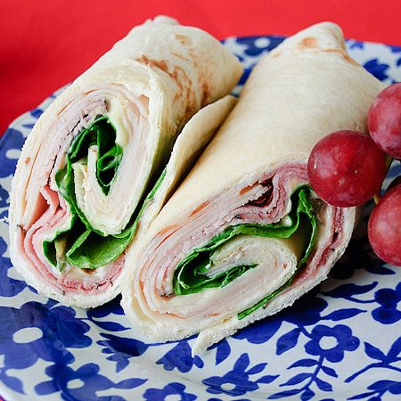Chicken Cordon Bleu Wraps    3/4 pound slice roasted chicken, from the deli  1/2 pound black forest ham, from the deli  4 wedges of creamy Swiss cheese such as Laughing Cow (or you can use spreadable cream cheese)  4 Tbsp mayonnaise  2 Tbsp  creamy honey Dijon mustard  1 cup baby spring mix lettuce or baby spinach  4 (8 inch) tortillas