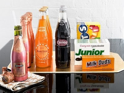 Set up a mini concessions bar for guests with jumbo packs of candy, old-fashioned sodas and mini bottles of bubbly