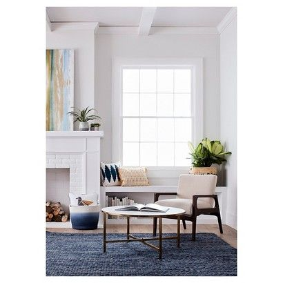 Here is how to create a comfy corner: ground the space with a blue rug, then add throw pillows and baskets in a mix of textures, neutrals and blues. Have a few small books stacked up beside modern bookends and add small art pieces or figurines for a personal touch.