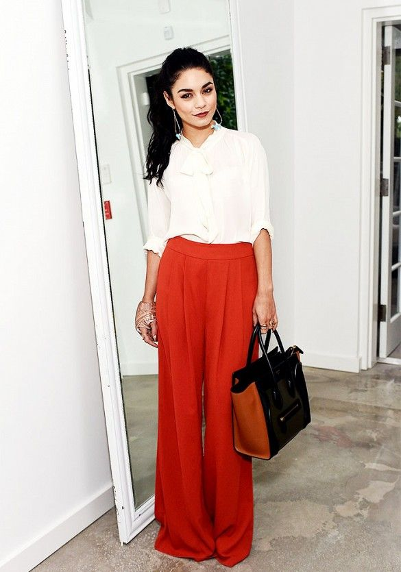 Vanessa Hudgens wears a white blouse, high-waisted wide-leg trousers, statement earrings, and a Céline bag