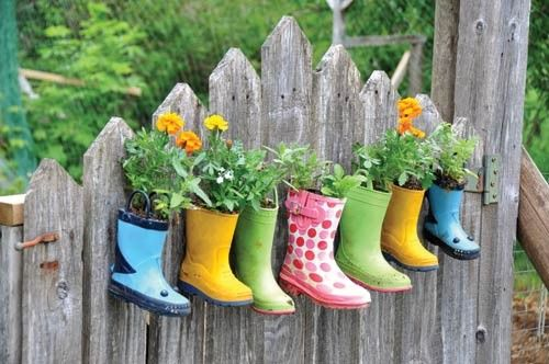 Garden Ideas: Rubber boots in a variety of colors become sturdy hanging planters when mounted on a fence.