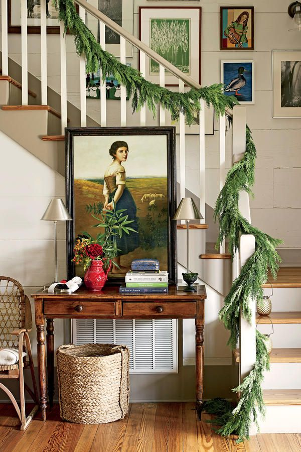 """The Entry - Pure Country Christmas Farmhouse - Southernliving. There's no formal foyer, so Ashley put together an entry moment with mystery and charm out of bits and pieces from far-flung locations. Posed against the staircase just beyond the front door is a mellowed wood table—a station for mail and keys. Two steel buffet lamps flank a leaning painting (of a farm girl) Ashley found 10 years ago on the street in Rome. """"The painting's rural setting and subject matter are made to feel heroic…"""