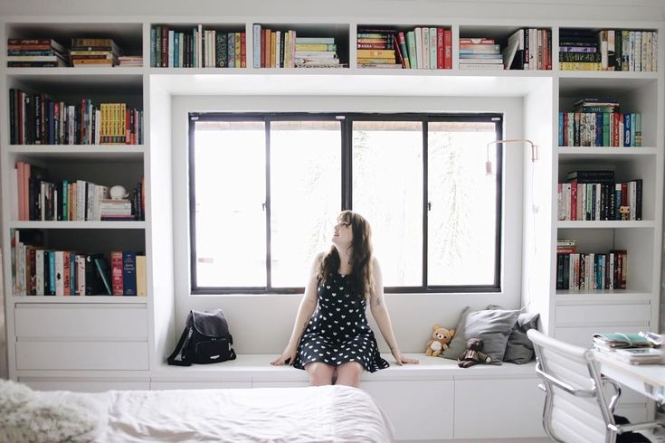 Estante de livro de Melina Souza do Serendipity. Feita sob medida. Branca, contorna a janela e tem lugar para sentar, deitar e ler.