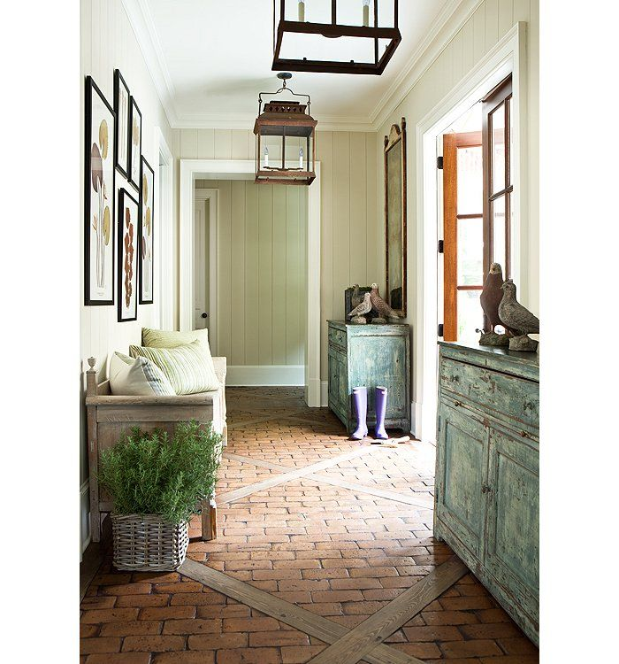 Classic French country-inspired entry with antique farmhouse furniture, iron pendant lights and patterned brick floor for easy sweeping!