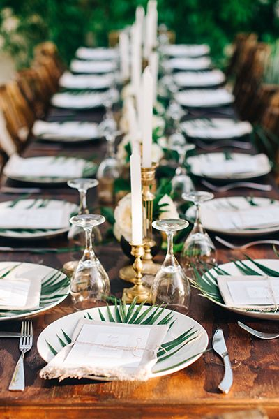 Fan palm leaf plate chargers bring a subtle tropical flair to a wedding tablescape set with rich wood and gilded candelabras, combining for refined rustic elegance.