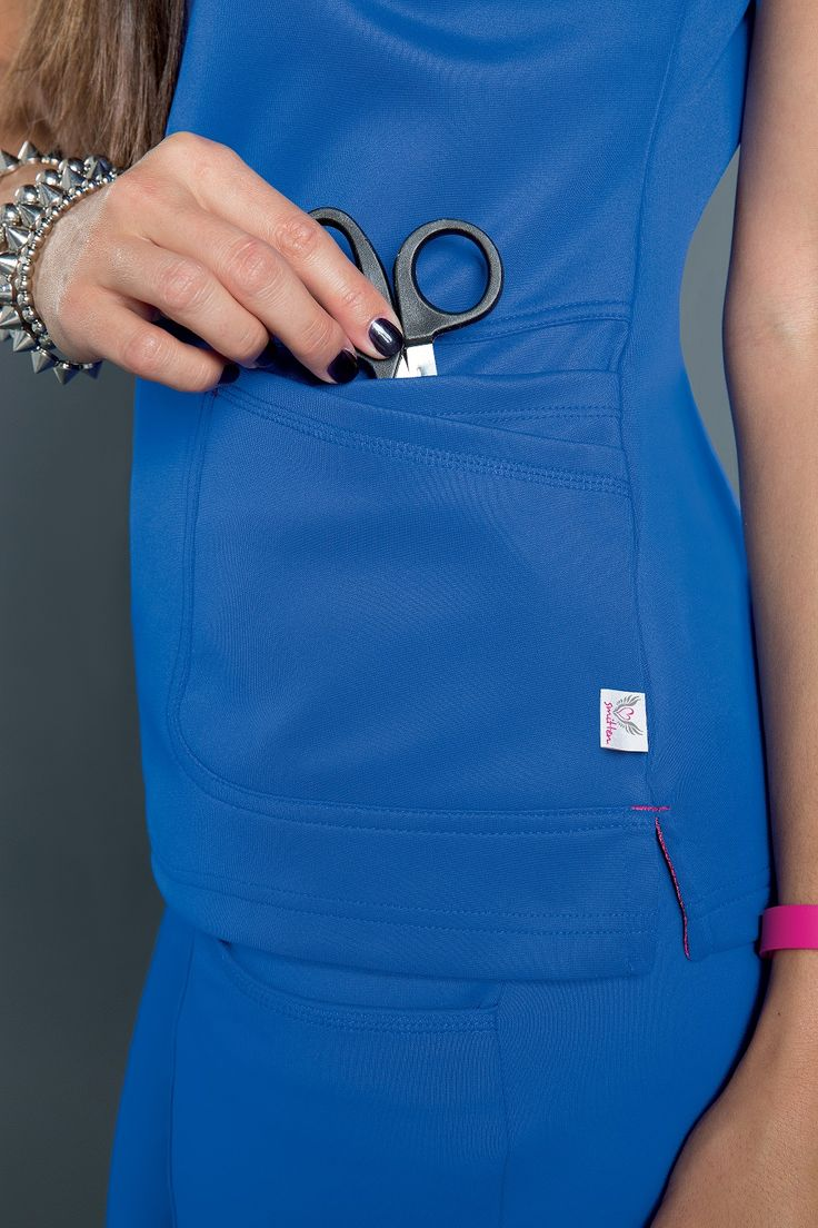 NEW! Smitten Bliss - Close-up front pocket storage on the S103008 RIOT Crossover Tunic. Available in Black, Navvy, Jazzberry and Royal. In-Stores Now. #smitten #scrubs #medical #fashion #uniforms #healthcare #medical #nurse #nursing #student #dental #vet #tech #cna #new #2016 #bliss #style #collection #rocknroll