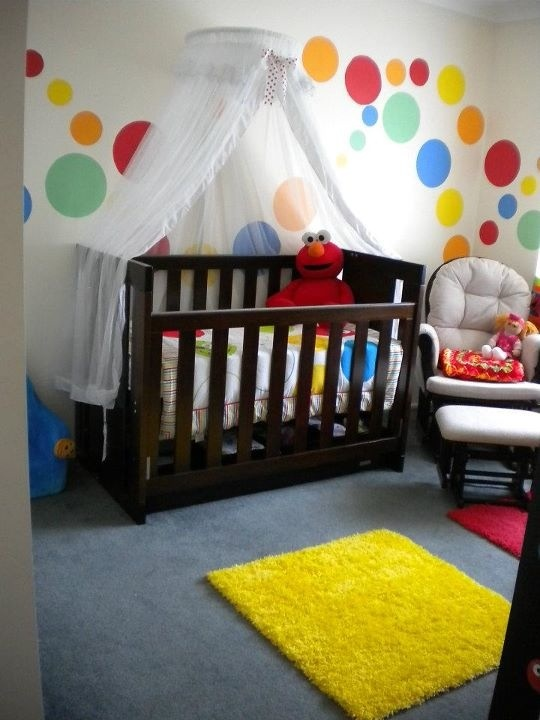 Baby nursery - love the colourful circles on the wall. I would only use a canopy like that when baby was very wee though, because after they can roll around or sit up, it would be a hazard.