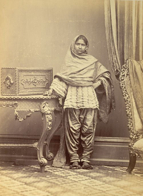 """Muslim girl from Karachi in Sindh, Pakistan, taken by Michie and Company in c. 1870, from the Archaeological Survey of India Collections. This is one of a series of photographs commissioned by the Government of India in the 19th century, in order to gather information about the dress, customs, trade and religions of the different racial groups on the sub-continent. The girl in the photograph demonstrates the method of wearing ear and nose rings, bracelets and anklets."""