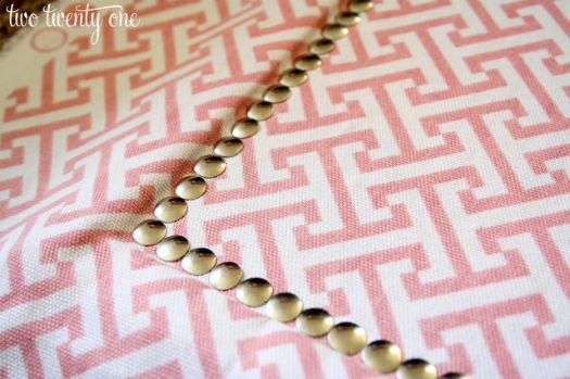 Covering Bulletin Board with Fabric and nail head trim (gold push pins)