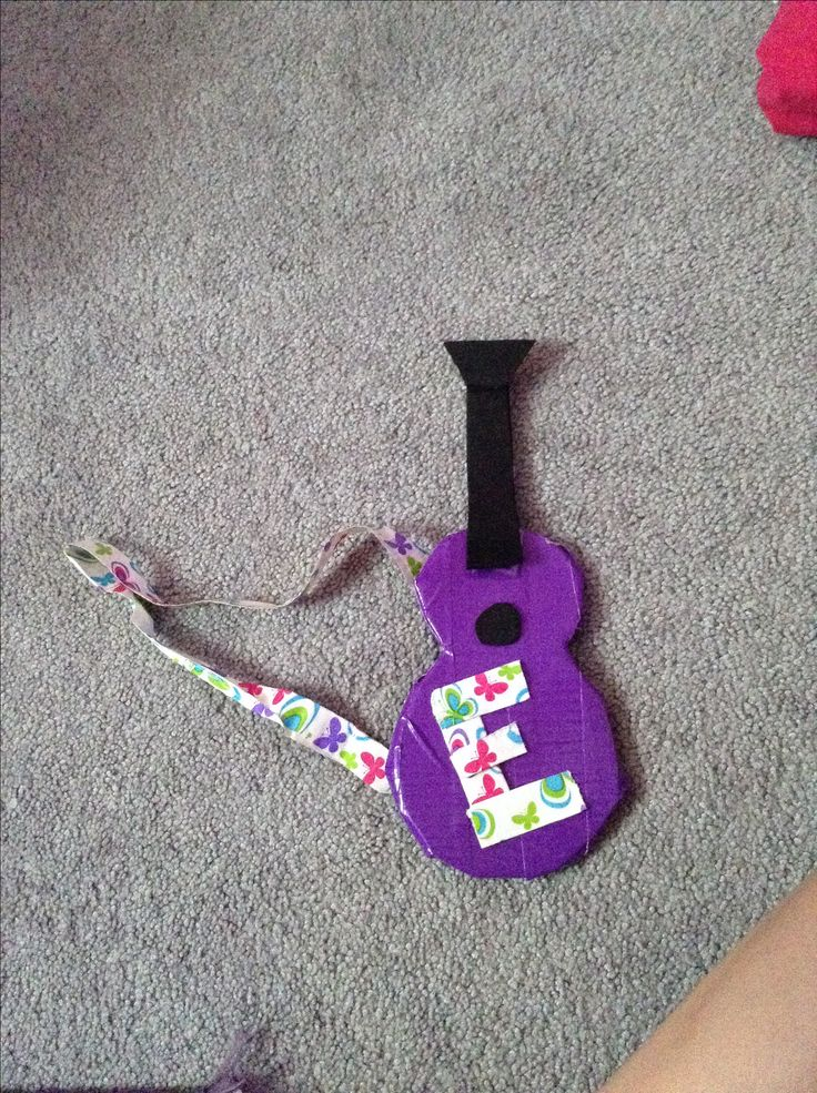 Easy American girl doll craft!!First I took two (one big one small ) bottle caps ,pressed them down and made impressions in the craft foam.Then I cut three of them out pelled off  the paper and layered them together and covered in duck tape .i cut 1 circle out two rectangles of black foam and stuck them together and placed them on the guitar .made an e for my dolls name Emily and strap out of duck tape and added two trapizods to the end of the rectangles