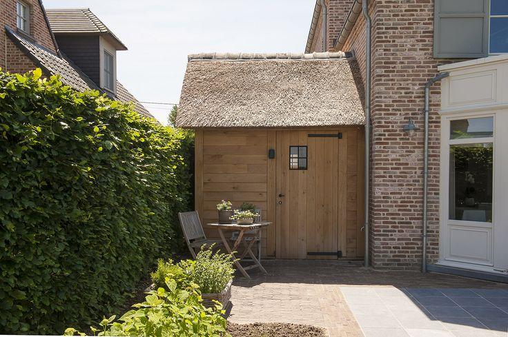 tuinberging met rieten dak - combinatie van kleiklinkers en arduin - Tuinaanleg De Pauw