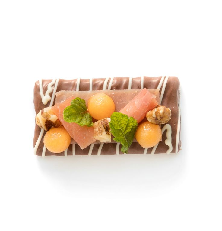 Cut the Serrano ham into strips, lay one strip on the Virtuoso and roll up two more. Cut the melon into balls using a Parisienne scoop and mix them with a tablespoon of walnut oil. Cut the walnuts into pieces and place them in between. Garnish with the walnuts and peppermint leaves.