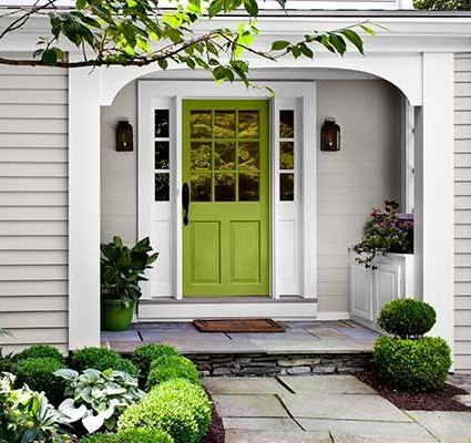 Soft green plays up details on a front door and vibrant foundation plantings. Behr's Fresh Apple.