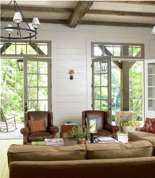 Horizontal plank walls, beamed ceilings, double French doors with transoms, out to a substantial porch
