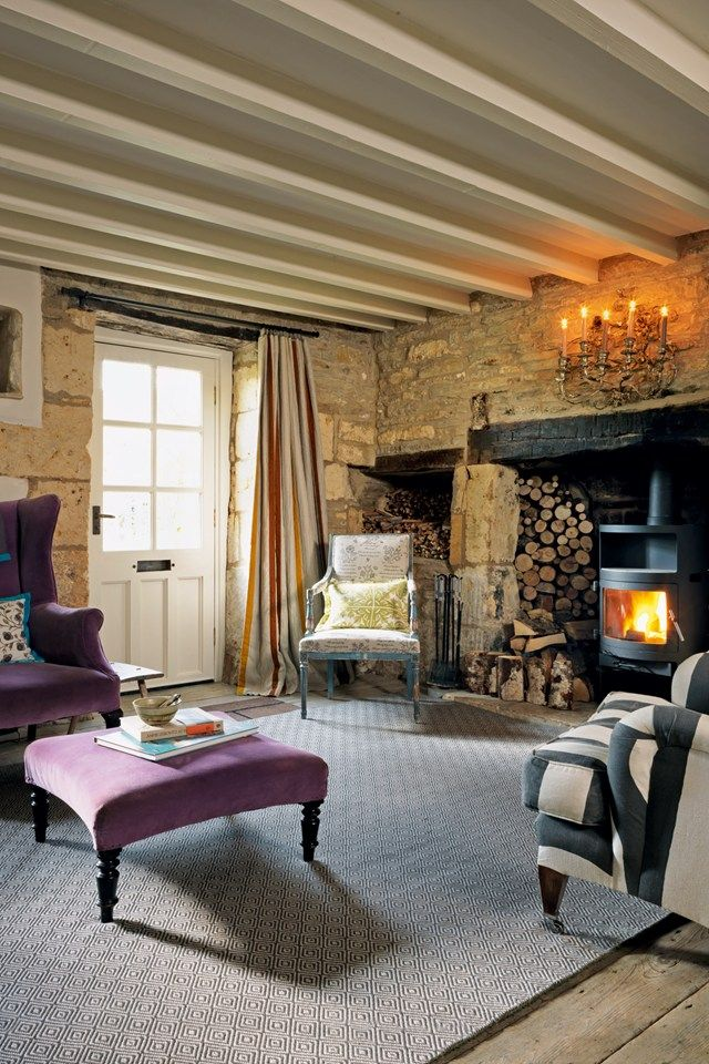 A steel and glass wood-burning stove from Scan warms the sitting room, while violet velvet upholstery from Emery & Cie on the armchair complements a Sinclair Till flatweave rug.
