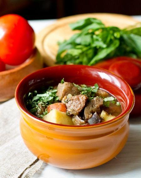 ЧАНАХИ  800 г баранины 2 средних баклажана (около 300 г каждый) 3-4 спелых помидора средних размеров 5-6 средних картофелин 4-5 луковиц 10 горошин черного перца 1/2 ч.л. красного молотого перца 2 ст.л. нарубленной кинзы 1 ст.л. нарубленного базилика 300 мл томатного сока соль по вкусу