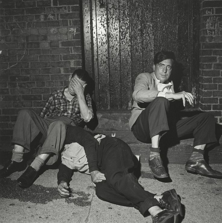 Three men slumped (or completely fallen) on a stoop--one looking at the camera, one covering his face with his hand, and the third seemingly unconscious with his whole head hidden by the face-coverer's leg, a puddle on the ground. Vivian Maier - Vivian Maier: Street Photographer, Revelation | LensCulture